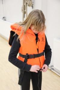 Tyttö pukee pelastusliivejä päälle liikuntasalissa.