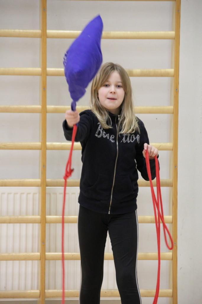 Tyttö heittää jumppakassia, jonka sisällä on hernepusseja painona ja harjoittelee vesipelastamista