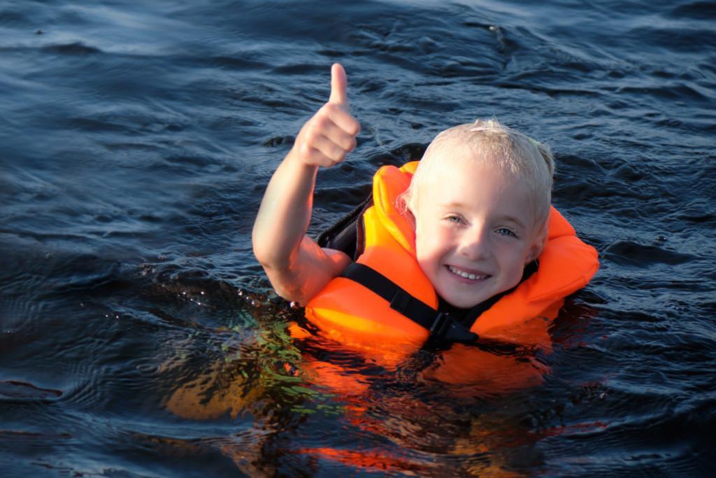 Poika ui pelastusliivit päällä meressä ja näyttää peukaloa.