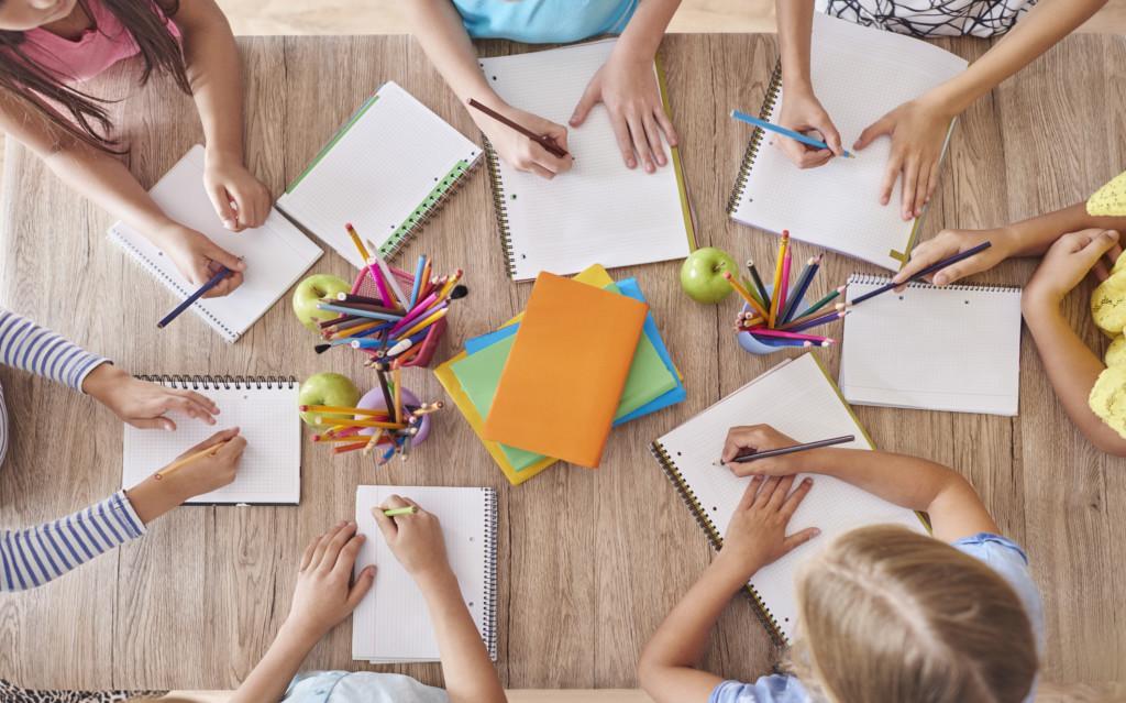 Kuva ylhäältäpäin. Lapset koulupöydän ääressä.