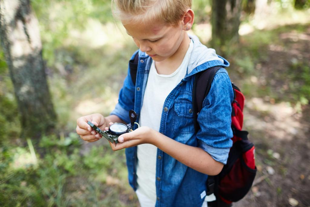 Poika sinisessä hupparissa ja reppuselässään katsoo kompassia kädessään.