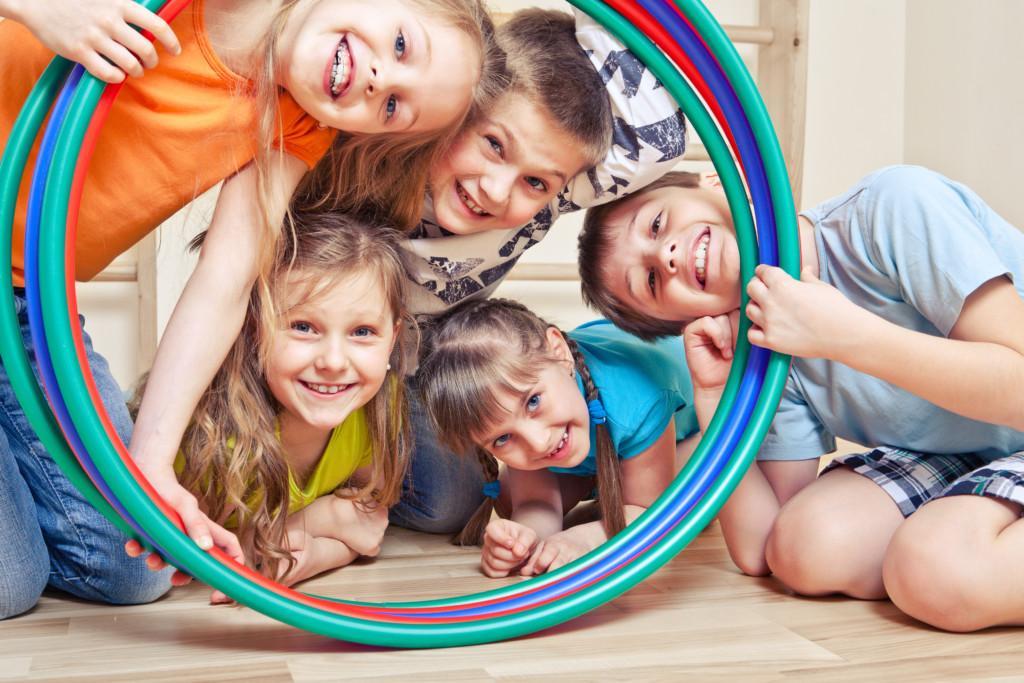 Lapset kurkkivat vanteiden läpi
