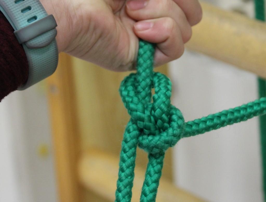 Käsi kiristää vihreään naruun tehtyä solmua.