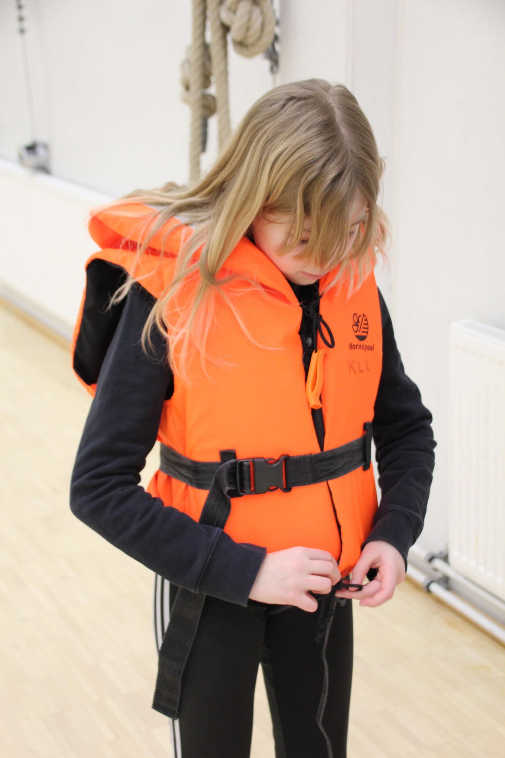 Tyttö pukee pelastusliiviä päälle koulun salissa.